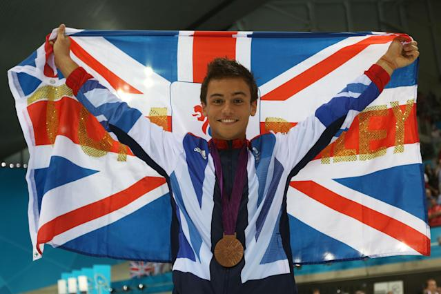 LONDON, ENGLAND - AUGUST 11: Bronze medallist Tom Daley of Great Britain poses with the national flag after the medal ceremony for the Men's 10m Platform Diving Semifinal on Day 15 of the London 2012 Olympic Games at the Aquatics Centre on August 11, 2012 in London, England. (Photo by Clive Rose/Getty Images)