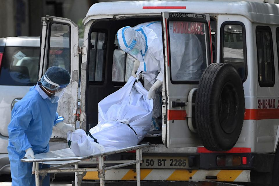 Hospital staff take out a body from an ambulance at a mortuary in New Delhi as India passes more than 300,000 deaths from coronavirus pandemic.