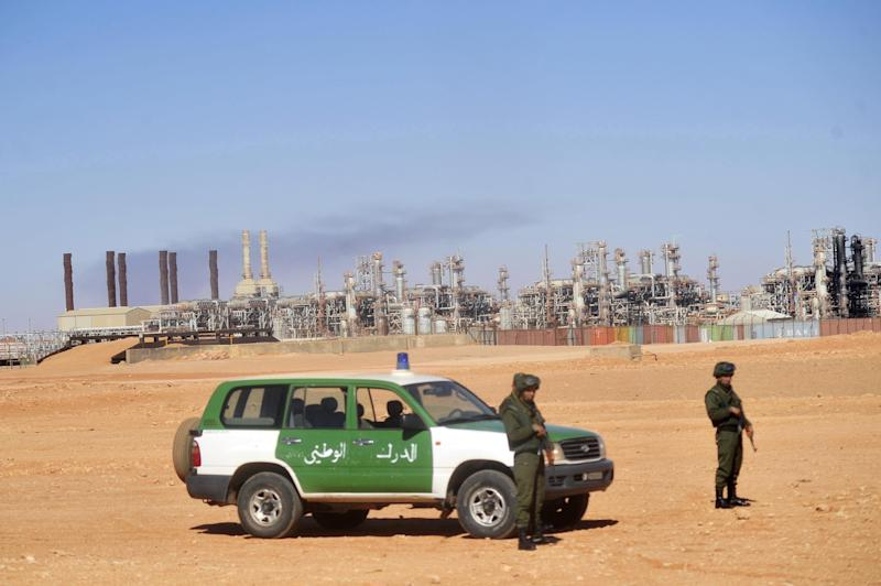 FILE - This  Jan. 31, 2013, file photo shows Algerian soldiers standing guard during a visit for news media organized by the Algerian authorities at the gas plant in Ain Amenas, seen on background. New corruption scandals are shining a fresh spotlight on Sonatrach, which jointly with BP and Norway's Statoil runs the desert gas plant that was the scene of a bloody hostage standoff last month. (AP Photo/File)