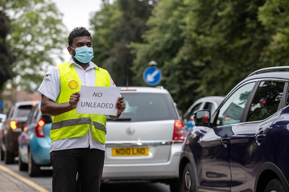 A Shell garage employee holds a sign on the side of the road informing a queue of traffic that they do not have unleaded petrol