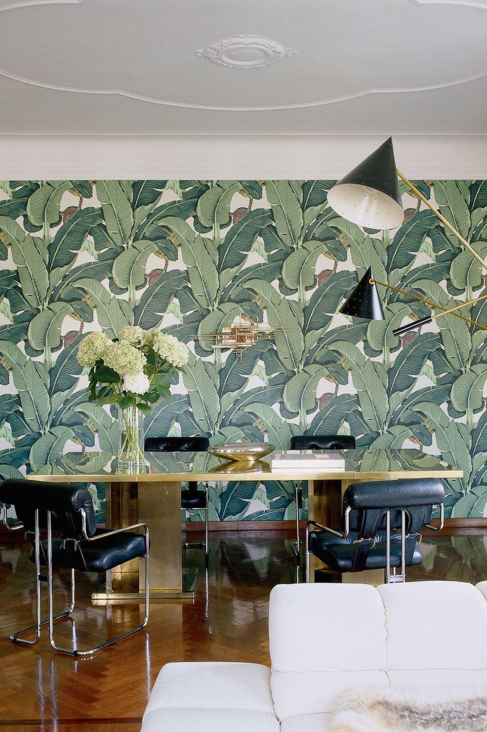 """<p>A palm-print wallcovering adds a dose of Southern California cool to the former Milan home of Brian Atwood and Nate Berkus. The brass dining table is from the 1970s.</p><p><em>Tropical Leaf Print Wallpaper, $60</em><br><a class=""""link rapid-noclick-resp"""" href=""""https://go.redirectingat.com?id=74968X1596630&url=https%3A%2F%2Fwww.westelm.com%2Fproducts%2Fwallshoppe-tropical-leaf-print-wallpaper-w2942%2F%3FcatalogId%3D71%26sku%3D4239221%26cm_ven%3DPLA%26cm_cat%3DGoogle%26cm_pla%3DWall%2BArt%2B%252B%2BMirrors%2B%253E%2BWallpaper%2B%252B%2BPaneling%26cm_ite%3D4239221%26gclid%3DCjwKCAjw8NfrBRA7EiwAfiVJpWRc3JXt1uf8sMGpGIXYhxoND8BVOOP4ZcygHkpqKQ3siJFX05j9jxoCSxQQAvD_BwE&sref=https%3A%2F%2Fwww.redbookmag.com%2Fhome%2Fg35083191%2Fwallpaper-design-ideas%2F"""" rel=""""nofollow noopener"""" target=""""_blank"""" data-ylk=""""slk:Shop the Look"""">Shop the Look</a></p>"""