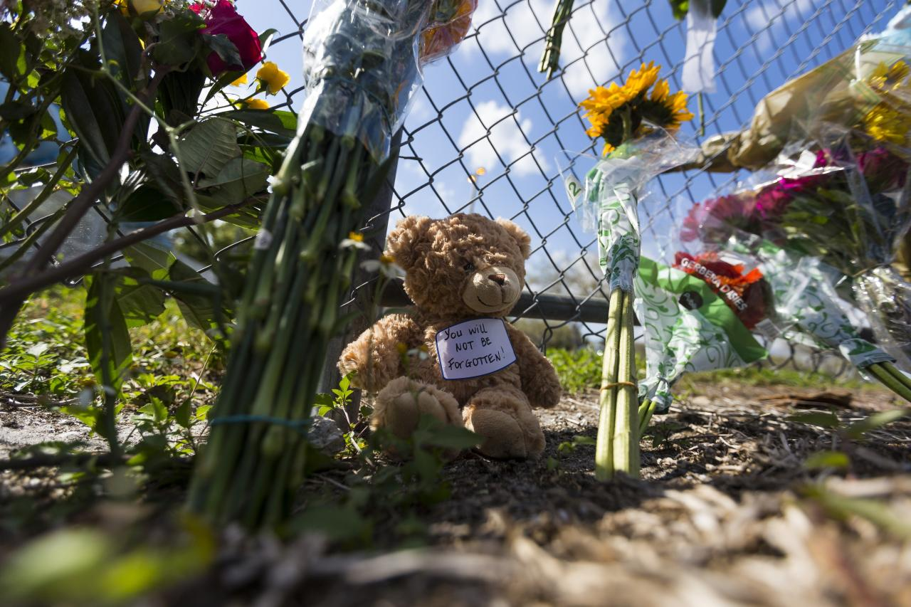 Mourners brought flowers, candles and stuffed animals to a makeshift memorial created by community members outside of Marjory Stoneman Douglas High School in Parkland, Fla., on Sunday, Feb. 18, 2018. A gunman entered the school last Wednesday and killed 17 students and teachers. (Matias J. Ocner/Miami Herald via AP)
