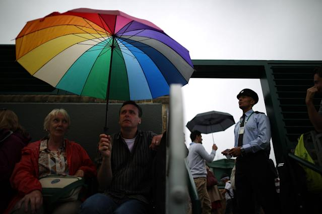 LONDON, ENGLAND - JUNE 27: Spectators and staff wait for play to resume on day four of the Wimbledon Lawn Tennis Championships at the All England Lawn Tennis and Croquet Club on June 27, 2013 in London, England. Play has been disrupted on some courts due to rain. (Photo by Peter Macdiarmid/Getty Images)