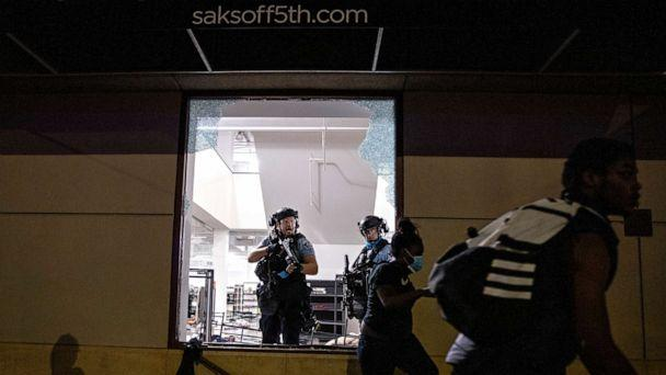 PHOTO: Police clear out and secure Saks OFF 5th after people broke in on Aug. 26, 2020, in Minneapolis. (Carlos Gonzalez/AP)