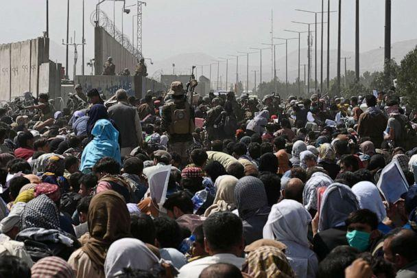 PHOTO: Afghans gather on a roadside near the military part of the airport in Kabul on August 20, 2021, hoping to flee from the country after the Taliban's military takeover of Afghanistan. (Wakil Kohsar/AFP via Getty Images)