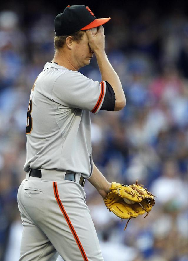 San Francisco Giants starting pitcher Matt Cain wipes his face after Los Angeles Dodgers' Matt Kemp hit a two-run home run in the fourth inning of a baseball game Sunday, April 6, 2014, in Los Angeles. (AP Photo/Alex Gallardo)