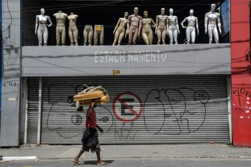 A homeless walks past a closed parking lot and mannequins in downtown Sao Paulo, Brazil, after the city government decreed the closure of shops and stores as a precautionary measure against the spread of the novel coronavirus COVID-19, on March 24, 2020