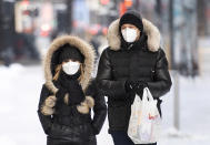 People wear face masks as they walk along a street in Montreal, Saturday, Jan. 23, 2021, as the COVID-19 pandemic continues in Canada and around the world. (Graham Hughes/The Canadian Press via AP)