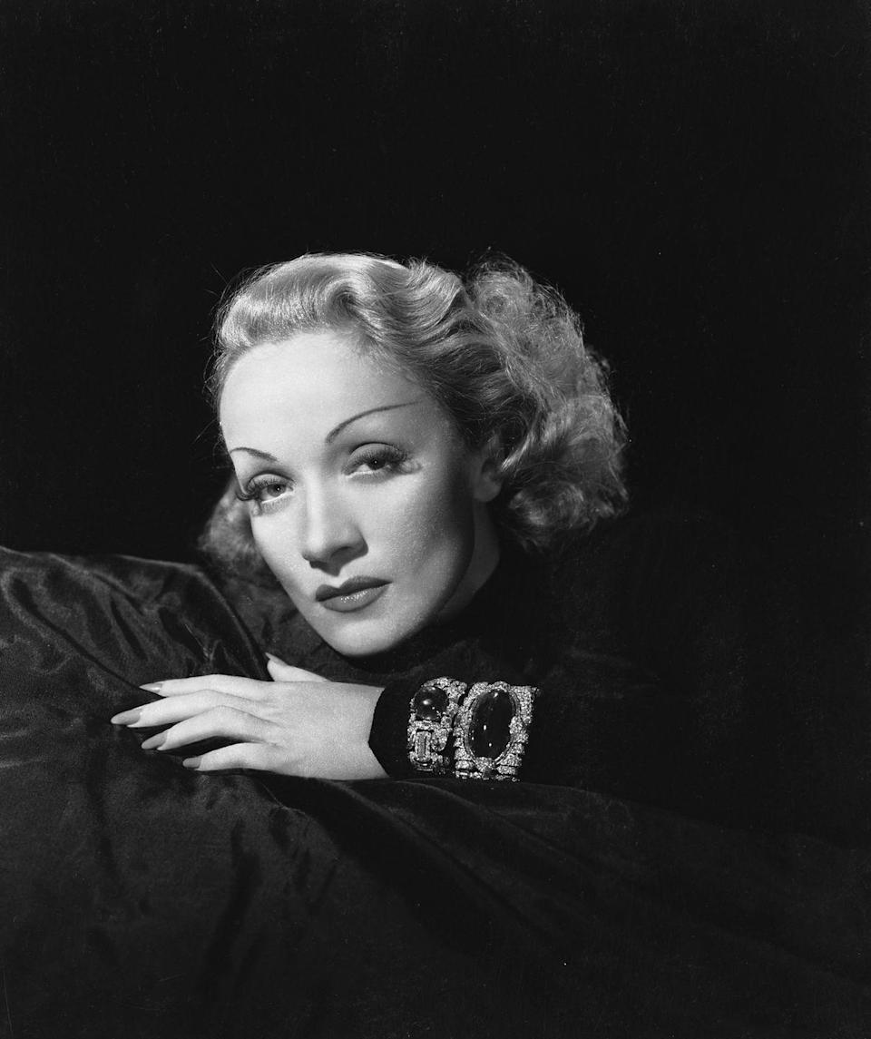 """<p>Dietrich, a known jewelry collector of many of the great designers and maisons, including <a href=""""https://www.cartier.com"""" rel=""""nofollow noopener"""" target=""""_blank"""" data-ylk=""""slk:Cartier"""" class=""""link rapid-noclick-resp"""">Cartier</a>, <a href=""""https://www.vancleefarpels.com/us/en/home.html"""" rel=""""nofollow noopener"""" target=""""_blank"""" data-ylk=""""slk:Van Cleef & Arpels"""" class=""""link rapid-noclick-resp"""">Van Cleef & Arpels</a>, and <a href=""""https://verdura.com"""" rel=""""nofollow noopener"""" target=""""_blank"""" data-ylk=""""slk:Verdura"""" class=""""link rapid-noclick-resp"""">Verdura</a>, is photographed here wearing her famous emerald-and-diamond bracelet. The piece, which was designed by Trabert & Hoeffer-Mauboussin, is set with a stunning 127-carat cabochon emerald.<br></p>"""