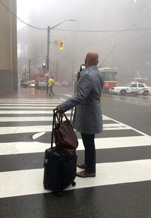 A pedestrian stands at a crosswalk as smoke rises near anintersection in the financial district after reports of a loud blast and heavy smoke could be seen in Toronto, Ontario, Canada May 1, 2017.  REUTERS/Anna Mehler Paperny