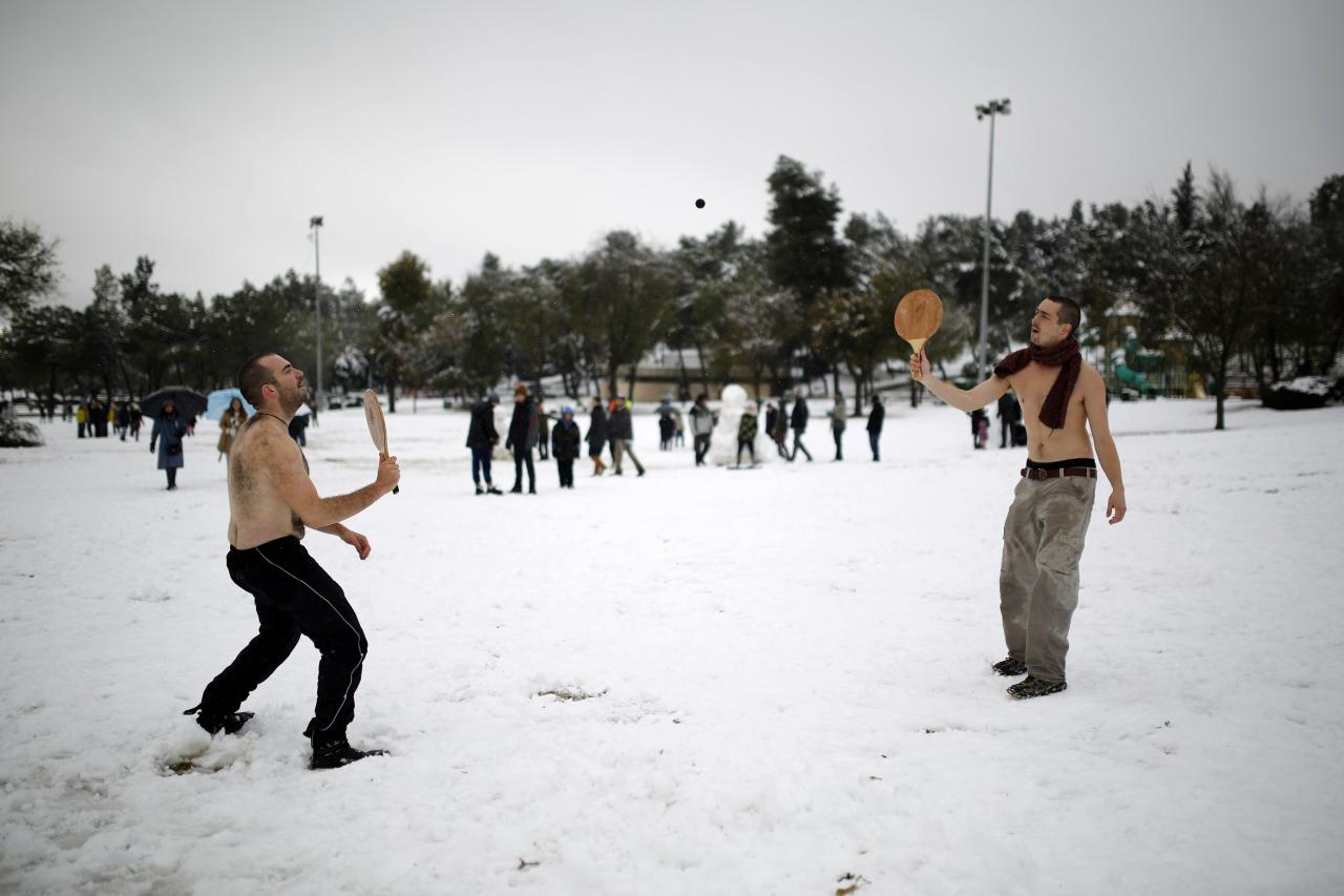 Men play a bat and ball game after a snowstorm at a park in Jerusalem December 12, 2013. Schools and offices in Jerusalem and parts of the occupied West Bank were closed and public transport briefly suspended after heavy snowfall on Thursday. REUTERS/Amir Cohen (JERUSALEM - Tags: ENVIRONMENT SOCIETY)
