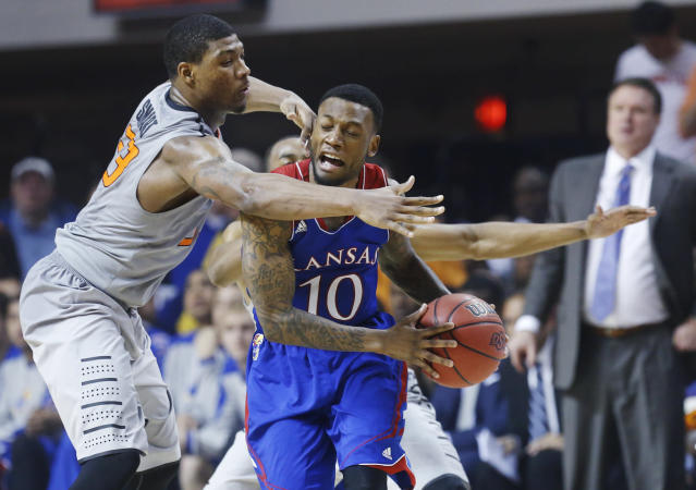 Oklahoma State guard Marcus Smart (33) pressures Kansas guard Naadir Tharpe (10) in the second half of an NCAA college basketball game in Stillwater, Okla., Saturday, March 1, 2014. Oklahoma State won 72-65. (AP Photo/Sue Ogrocki)