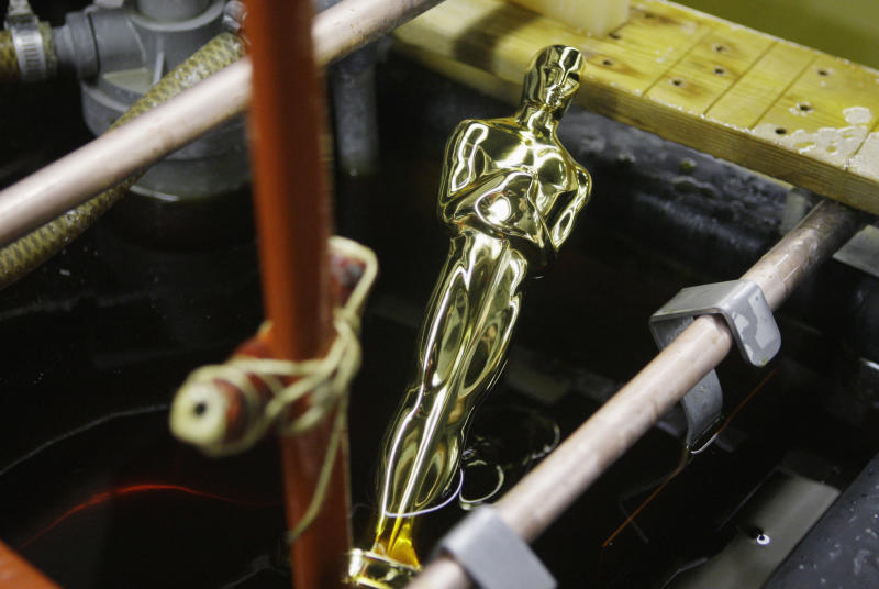 FILE - In this Jan. 26, 2009 file photo, an Oscar statue is pulled from the final plating process that coats the statue with 24-karat gold at R.S. Owens & Co., in Chicago. The company said it will be laying off 95 workers on Dec. 17, 2012. The cuts come a month after the company announced it was being purchased on Dec. 17 by St. Regis Crystal Inc. of Indianapolis. They have about 250 employees. A news release on the sale said the company will continue to make Oscar and Emmy statues in Chicago. They have been making the Oscar statues for about 30 years. (AP Photo/M. Spencer Green, File)