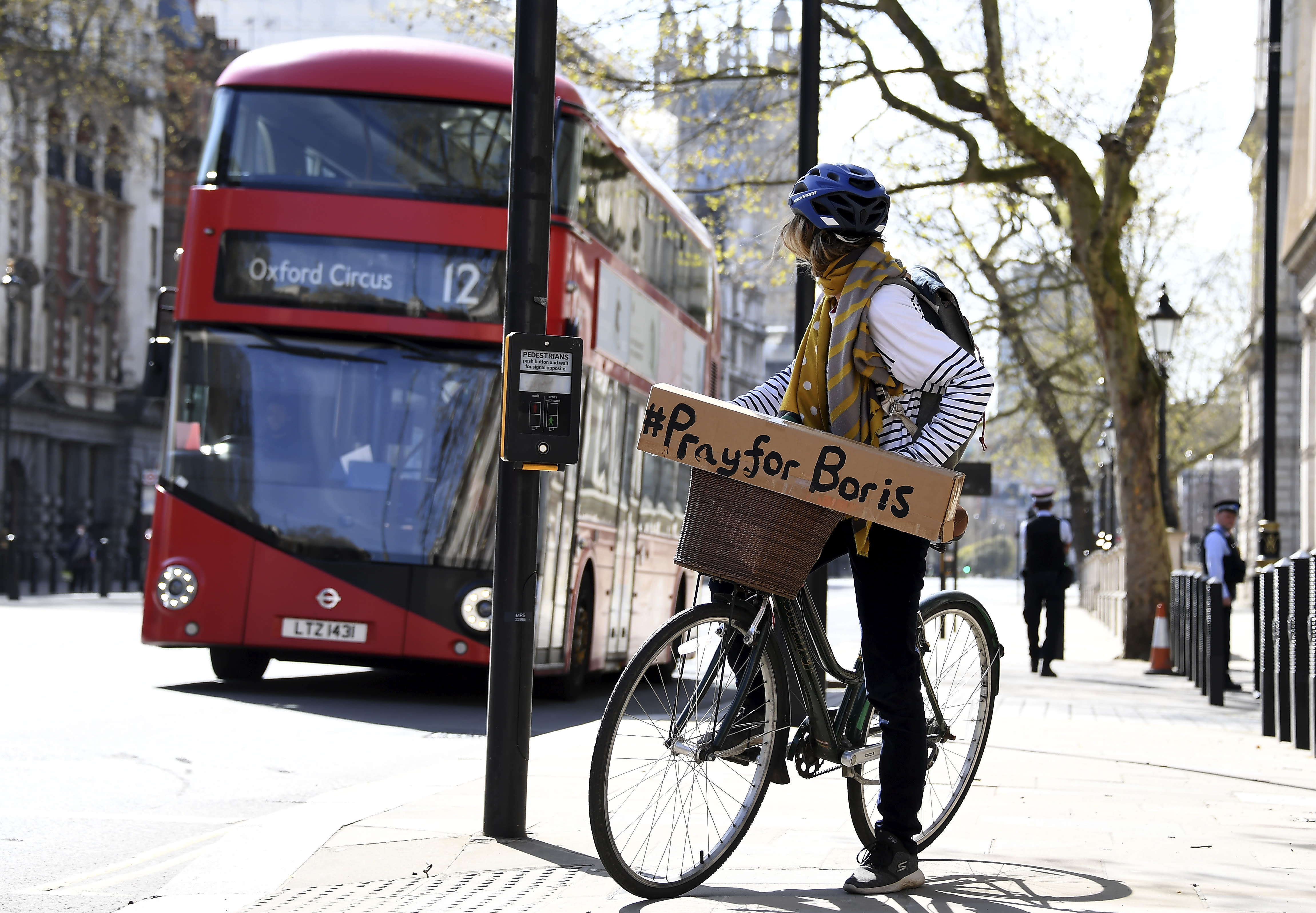 A woman shows a sign on her bicycle as British Prime Minister Boris Johnson is in intensive care fighting the coronavirus in London, Tuesday, April 7, 2020. Johnson was admitted to St Thomas' hospital in central London on Sunday after his coronavirus symptoms persisted for 10 days. Having been in hospital for tests and observation, his doctors advised that he be admitted to intensive care on Monday evening. The new coronavirus causes mild or moderate symptoms for most people, but for some, especially older adults and people with existing health problems, it can cause more severe illness or death.(AP Photo/Alberto Pezzali)