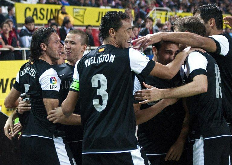 Malaga's Martin Demichelis (L) celebrates with teammates after scoring a goal against Sevilla during their Spanish La Liga match at the Ramon Sanchez Pizjuan stadium in Sevilla, on December 15, 2012. Malaga won 2-0