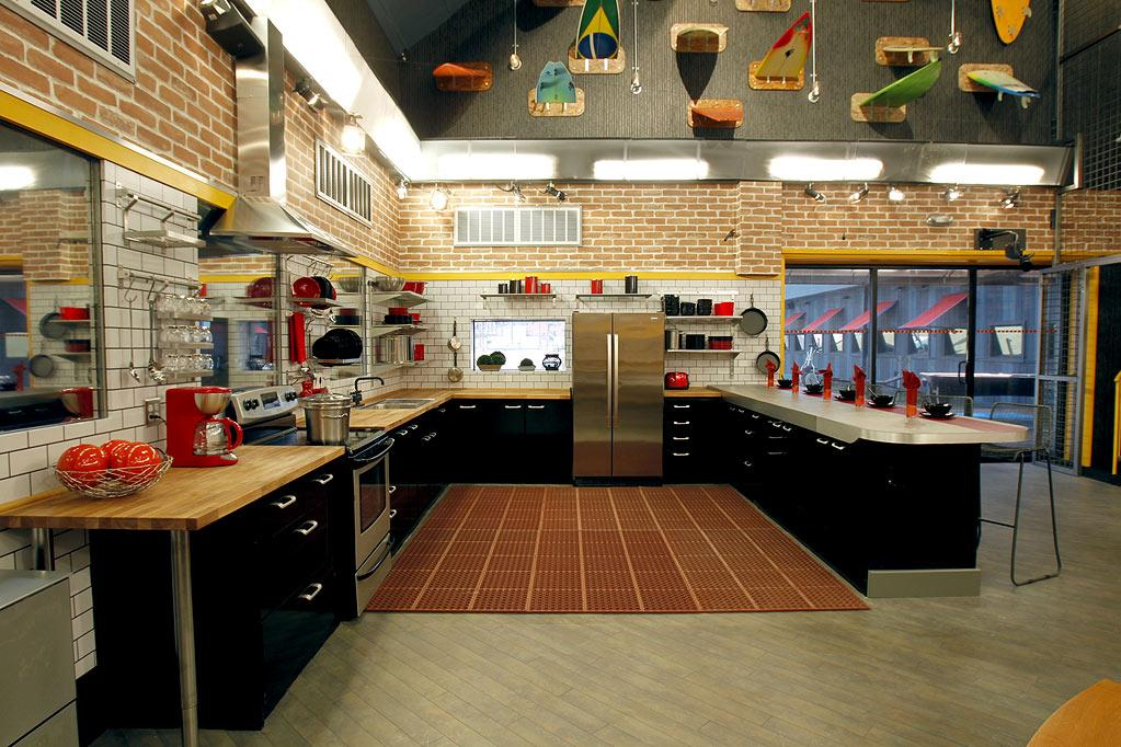 """The layout of the kitchen hasn't changed since <a href=""""http://tv.yahoo.com/slideshow/584/photos/1"""" rel=""""nofollow"""">the previous season</a>, but there are a few new features to point out: Butcher-block counters replace last year's blue Formica ones; a window (you can actually see out of and into the backyard) is next to the fridge; and 17 (not that we're counting!) surfboards protrude from the wall above the sliding glass doors."""