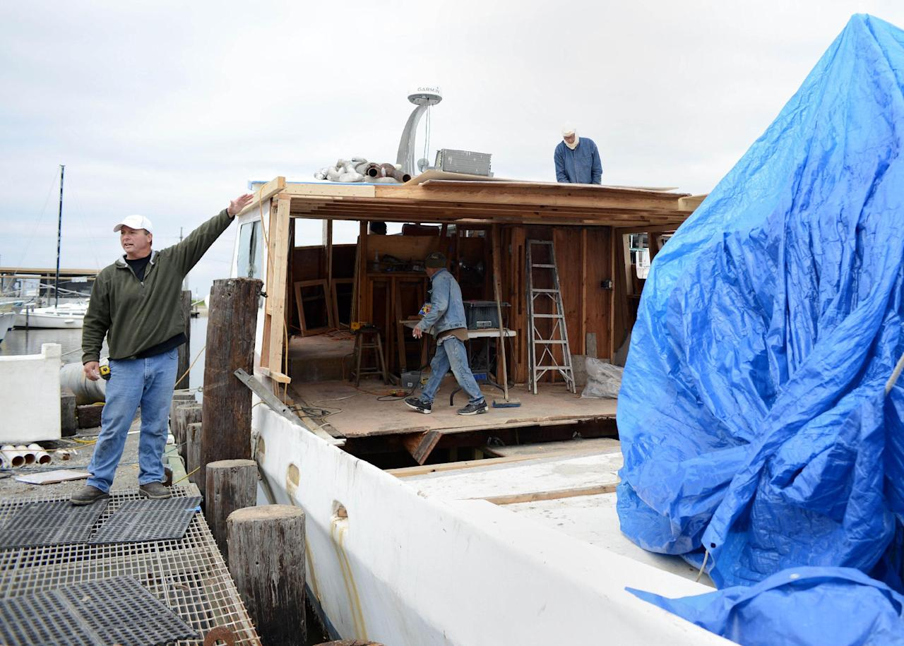 CORRECTS SPELLING - Bert Ducote talks about performing cleanup work with his boat during the Deepwater Horizon oil spill. The boat is being rebuilt at the Lake Catherine Marina in New Orleans, Friday, March 7, 2014. Ducote has had dozens of boils pop up on his skin since helping to work the oil spill cleanup. (AP Photo/Andrea Mabry)
