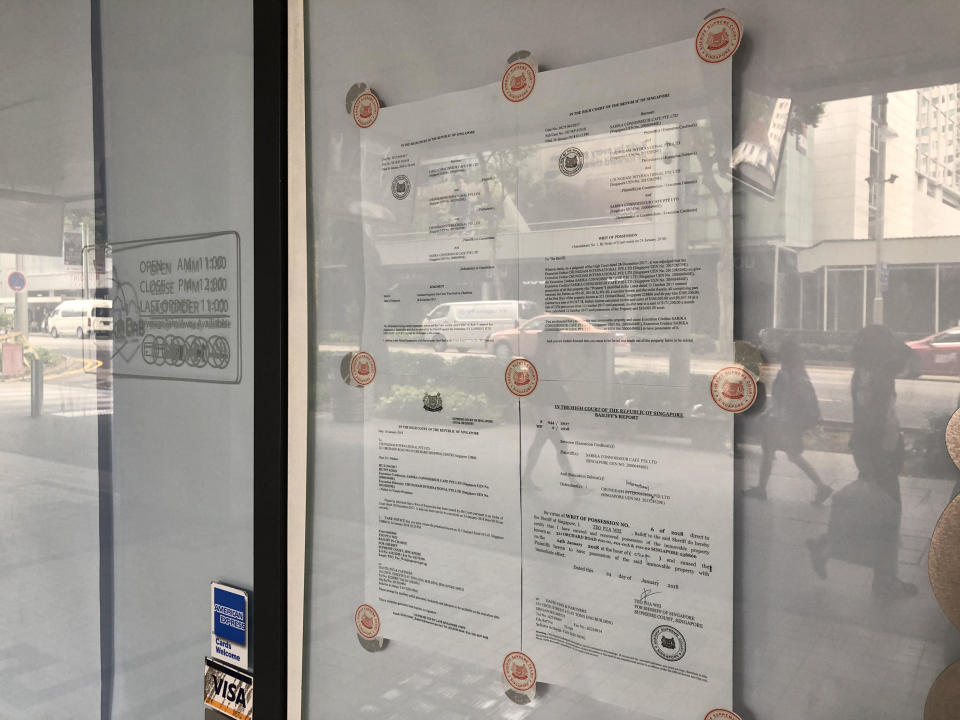 Legal documents issued by the High Court were pasted on the glass doors of Ice Lab Cafe's Orchard outlet. (Photo: Nurul Azliah/Yahoo Lifestyle Singapore)