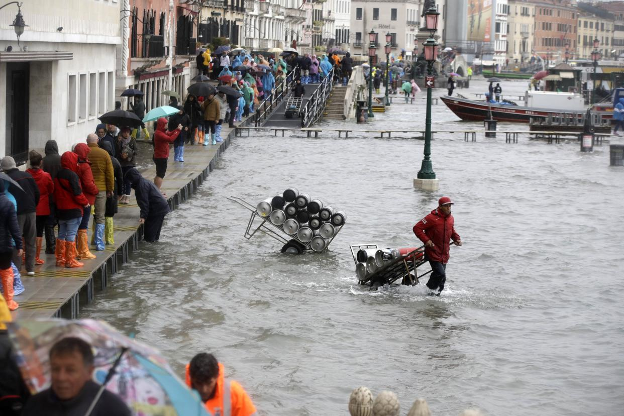 People walk on catwalks set up on the occasion of a high tide, in a flooded Venice, Italy, Tuesday, Nov. 12, 2019. (Photo: Luca Bruno/AP)