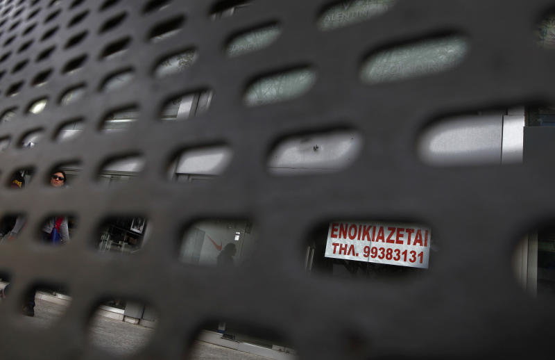 Seen through a bus stop bench, a woman passes an empty shop with a sign reading in Greek 'for rent' in central capital Nicosia, Cyprus, on Saturday, March 30, 2013. Big depositors at Cyprus' largest bank may be forced to accept losses of up to 60 percent, far more than initially estimated under the European rescue package to save the country from bankruptcy, officials said Saturday. (AP Photo/Petros Karadjias)