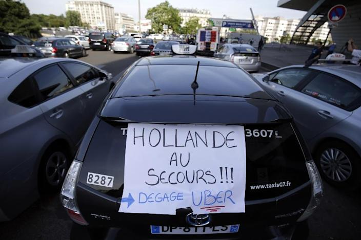 """A sign on a taxi reads """"Hollande help! Get rid of Uber"""" as taxi drivers block Porte Maillot in Paris on June 25, 2015 (AFP Photo/Kenzo Tribouillard)"""