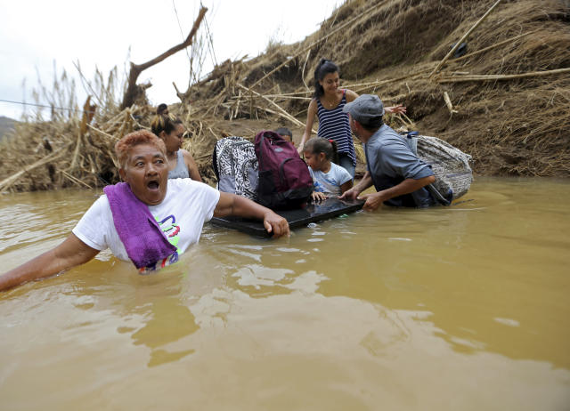 <p>Marta Sostre Vazquez reacts as she starts to wade into the San Lorenzo Morovis river with her family, after the bridge was swept away by Hurricane Maria, in Morovis, Puerto Rico, Wednesday, Sept. 27, 2017. The family was returning to their home after visiting family on the other side. (Photo: Gerald Herbert/AP) </p>