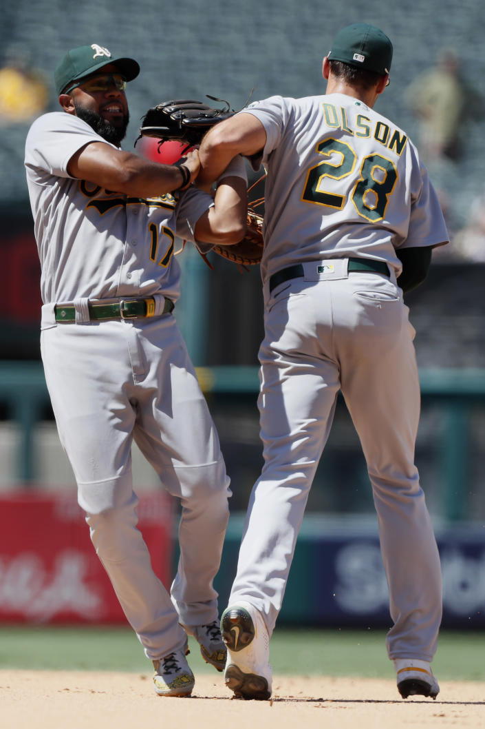 Oakland Athletics shortstop Elvis Andrus, left, wins the battle to catch a fly ball with first baseman Matt Olson hit by Los Angeles Angels' Kurt Suzuki during the sixth inning of a baseball game in Anaheim, Calif., Saturday, July 31, 2021. (AP Photo/Alex Gallardo)