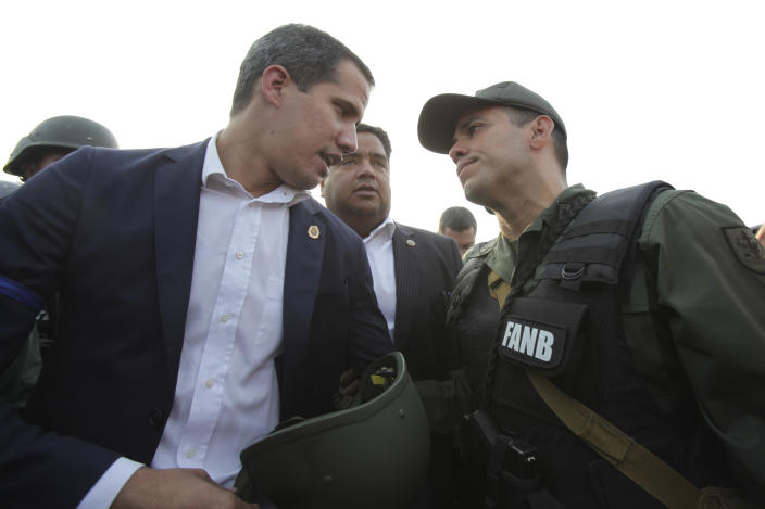 FILE - In this April 30, 2019 file photo, Juan Guaido, Venezuela's opposition leader and self proclaimed president, talks to Lt. Col. Rafael Soto of the National Guard, outside La Carlota air base in Caracas, Venezuela. On April 30, a group of Bolivarian National Guardsmen shocked Venezuelans and the world alike by appearing with tanks and heavily-armed troops on a bridge in eastern Caracas alongside Guaido and activist Leopoldo Lopez, who they helped spring from what they considered an illegal house arrest. (AP Photo/Boris Vergara, File)