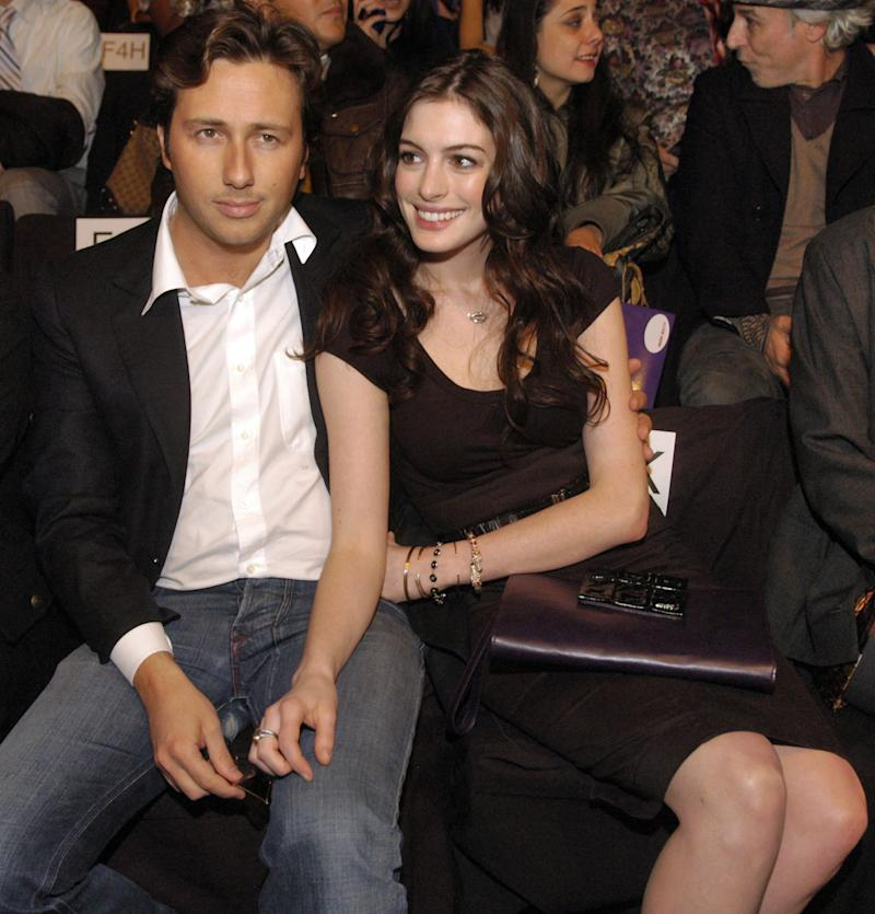 """FILE - In this Feb. 3, 2008, file photo, actress Anne Hathaway, right, sits with her boyfriend, Raffaello Follieri, at the Miss Sixty fashion show during fashion week in New York. Follieri was released Friday morning from a prison in Loretto, 80 miles east of Pittsburgh. Follieri pleaded guilty to cheating investors by falsely claiming he had Vatican connections that enabled him to buy church property at a discount. He was sentenced in 2008 to 4 1/2 years in prison. Follieri agrees he owes more than $3.6 million to those he ripped off. The proceeds supported a playboy lifestyle that included a $37,000-a-month New York City apartment and lavish vacations with Hathaway, the star of """"The Princess Diaries."""" (AP Photo/Brian McDermott)"""