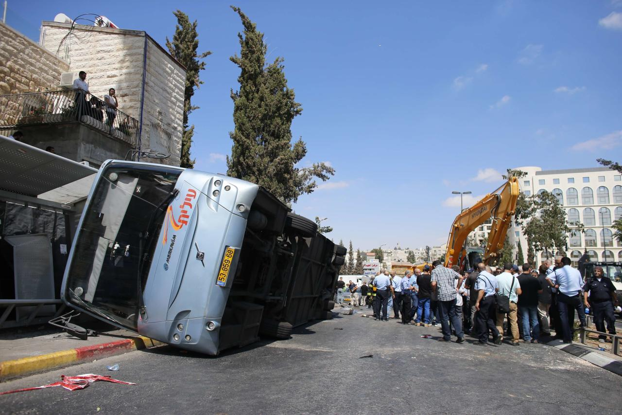 An overturned bus lies at the scene of a suspected attack in Jerusalem August 4, 2014. A construction vehicle hit and killed a pedestrian and overturned the bus on a main street in Jerusalem on Monday in what police suspect was a Palestinian attack, which ended when policemen shot dead the driver of the yellow excavator. REUTERS/Ammar Awad (JERUSALEM - Tags: POLITICS CIVIL UNREST)