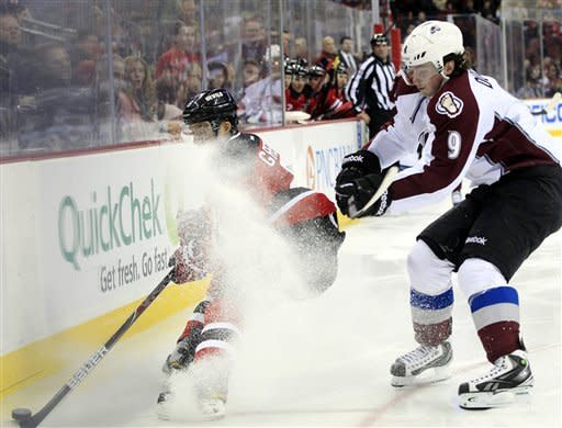 New Jersey Devils' Andy Greene, left, tries to keep the puck away from Colorado Avalanche's Matt Duchene (9) during the first period of an NHL hockey game in Newark, N.J., Thursday, March 15, 2012. (AP Photo/Mel Evans)