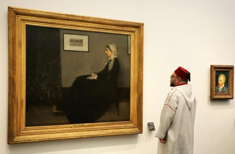 """Moroccan King Mohammed VI looks at a painting titled """"Whistler's Mother"""" by James Abbott McNeill Whistler (1871) at the November 2017 opening of the Louvre Abu Dhabi Museum"""