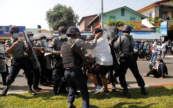 A demonstrator is detained by police officers during a protest against the military coup in Mawlamyine - THAN LWIN TIMES/via REUTERS