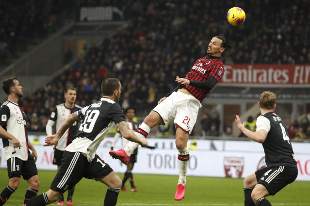 AC Milan's Zlatan Ibrahimovic, jumps for the ball by Juventus players during an Italian Cup soccer match between AC Milan and Juventus at the San Siro stadium, in Milan, Italy, Thursday, Feb. 13, 2020. (AP Photo/Antonio Calanni)
