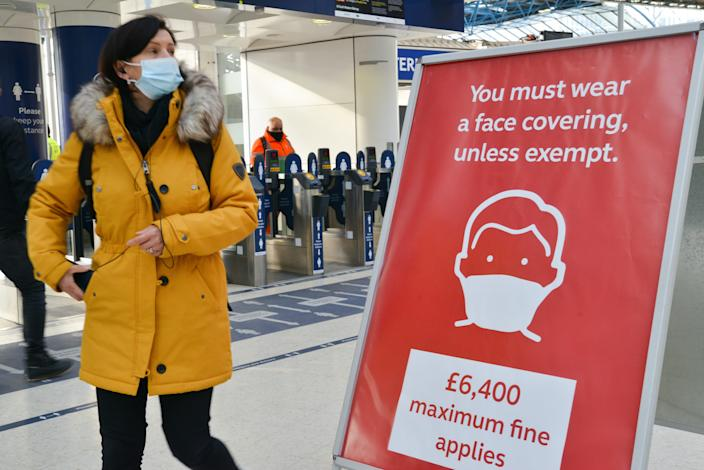 Commuter wearing a face mask walks past a sign reminding the public about a fine for not wearing a face mask, after arriving at London Waterloo railway station in London. Prime Minister Boris Johnson announced that there was evidence that the new variant of the coronavirus is more deadly. (Photo by Thomas Krych / SOPA Images/Sipa USA)