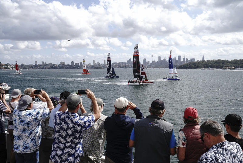 Spectators watch the action from a boat as Britain's boat, center, helmed by Ben Ainslie leads the fleet in the first race of the Sydney SailGP event on Sydney Harbour, Friday, Feb. 28, 2020. (Thomas Lovelock/SailGP via AP)