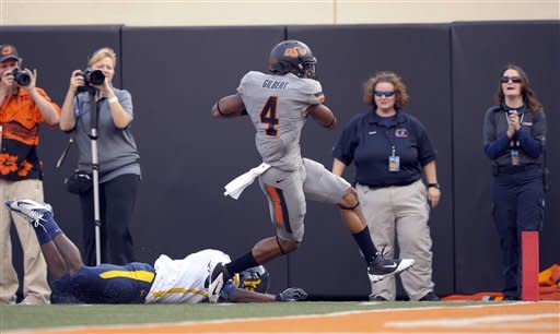 West Virginia's Nana Kyeremeh, left, fails to stop Oklahoma State's Justin Gilbert, right, from returning a kickoff for 96 yards and a touchdown during the first half of an NCAA college football game in Stillwater, Okla., Saturday, Nov. 10, 2012.(AP Photo/Brody Schmidt)