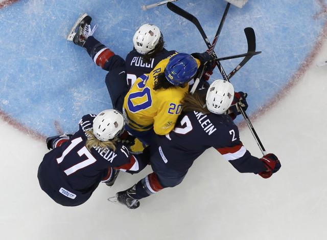 Sweden's Fanny Rask (C) is squeezed out by three Team USA players during the third period of their women's semi-final ice hockey game at the Sochi 2014 Winter Olympic Games, February 17, 2014. REUTERS/Mark Blinch (RUSSIA - Tags: OLYMPICS SPORT ICE HOCKEY)