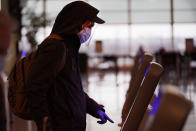 FILE - In this Nov. 24, 2020 file photo, an air traveler checks in wearing a protective mask, face shield and protective gloves, for his flight on Southwest Airlines at Midway Airport in Chicago. As few people traveled, the airline industry needed billions of dollars in aid from the government and is still threatening to lay off workers.(AP Photo/Charles Rex Arbogast)