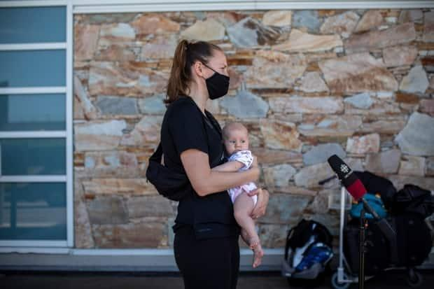 Team Canada basketball player Kim Gaucher is pictured with her daughter Sophie outside of Vancouver International Airport earlier in June. On Wednesday, the Tokyo Organizing Committee announced Olympians would be allowed to bring newborns like Sophie to Japan. (Ben Nelms/CBC - image credit)