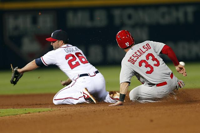 St. Louis Cardinals shortstop Daniel Descalso (33) steals second base as the ball gets past Atlanta Braves second baseman Dan Uggla (26) in the seventh inning of a baseball game, Tuesday, May 6, 2014, in Atlanta. (AP Photo/John Bazemore)