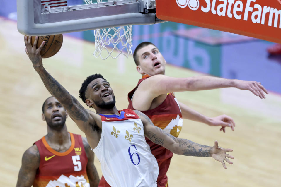 New Orleans Pelicans guard Nickeil Alexander-Walker (6) shoots a basket as Denver Nuggets center Nikola Jokic (15) defends in the second half of an NBA basketball game in New Orleans, Friday, March 26, 2021. (AP Photo/Rusty Costanza)