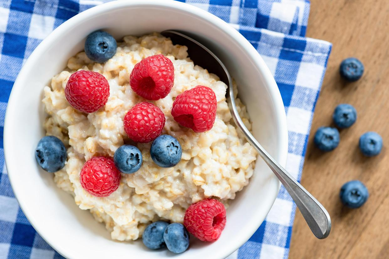 Oatmeal porridge with fresh berries, raspberry and blueberry. Closeup view, top view. Healthy eating, healthy breakfast, nutrition concept