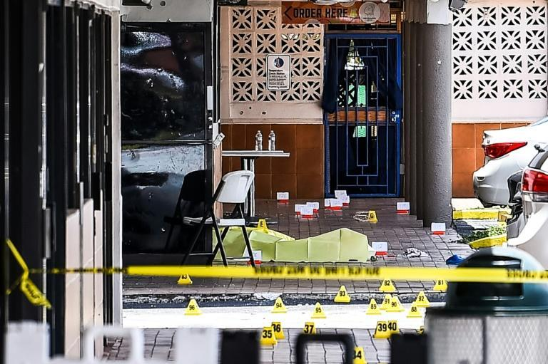 A body is seen outside a hall that was rented for a concert, after three gunmen killed two people and injured 20 overnight in the Hialeah area of Miami Dade county on May 30 2021