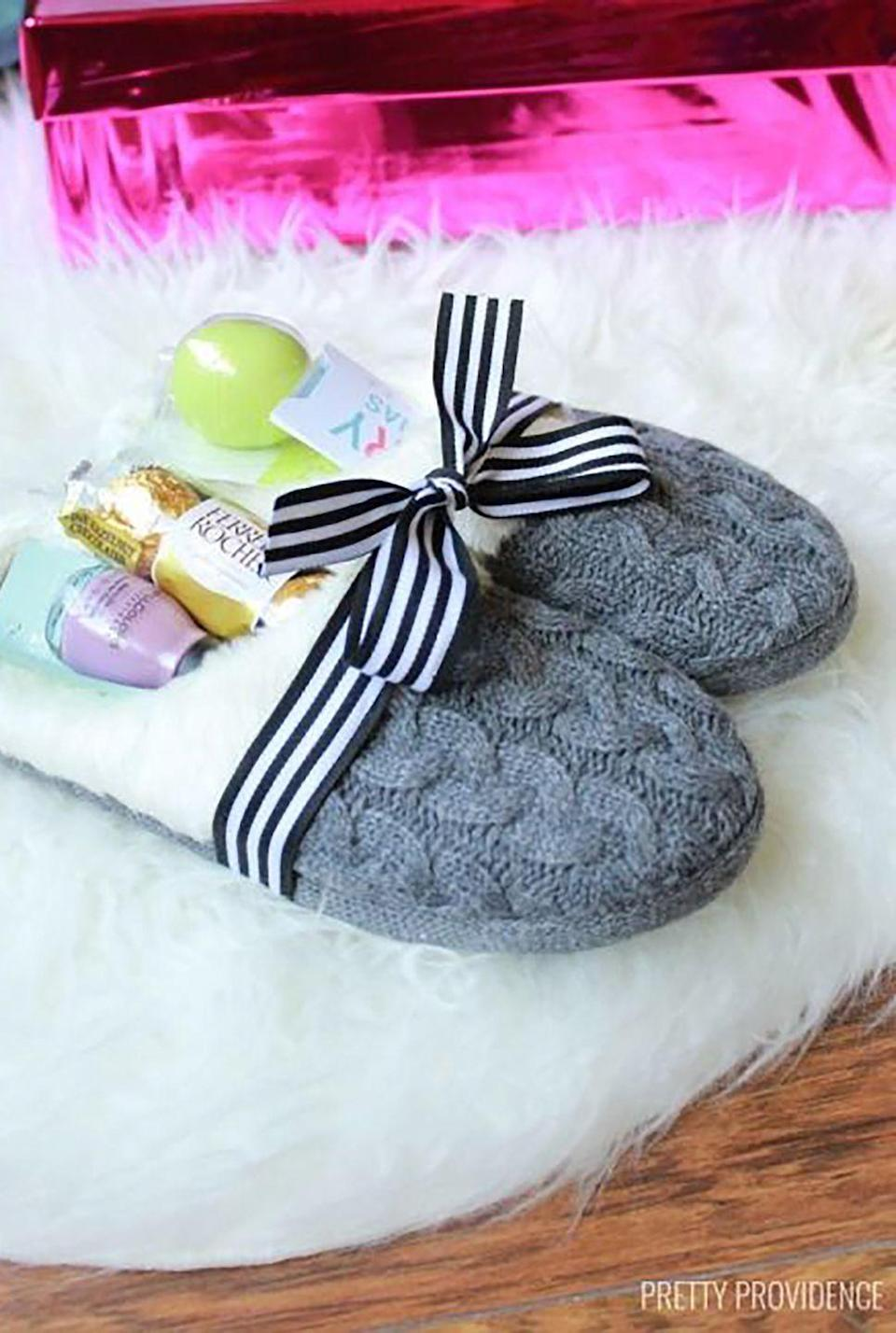 """<p>Fill a pair of cozy slippers with goodies, such as <a href=""""https://www.amazon.com/dp/B00BXS0NKU?ref_=ams_ad_dp_asin_1&tag=syn-yahoo-20&ascsubtag=%5Bartid%7C10050.g.645%5Bsrc%7Cyahoo-us"""" rel=""""nofollow noopener"""" target=""""_blank"""" data-ylk=""""slk:nail polish"""" class=""""link rapid-noclick-resp"""">nail polish</a>, candy, or <a href=""""https://www.amazon.com/Burts-Bees-Natural-Moisturizing-Beeswax/dp/B0054LHI5A?tag=syn-yahoo-20&ascsubtag=%5Bartid%7C10050.g.645%5Bsrc%7Cyahoo-us"""" rel=""""nofollow noopener"""" target=""""_blank"""" data-ylk=""""slk:lip balm"""" class=""""link rapid-noclick-resp"""">lip balm</a>. </p><p><strong>Get the tutorial at <a href=""""http://prettyprovidence.com/slippers-gift-idea/"""" rel=""""nofollow noopener"""" target=""""_blank"""" data-ylk=""""slk:Pretty Providence"""" class=""""link rapid-noclick-resp"""">Pretty Providence</a>.</strong></p><p><strong><a class=""""link rapid-noclick-resp"""" href=""""https://www.amazon.com/slp/knit-slippers/nakqktv7mggd562?tag=syn-yahoo-20&ascsubtag=%5Bartid%7C10050.g.645%5Bsrc%7Cyahoo-us"""" rel=""""nofollow noopener"""" target=""""_blank"""" data-ylk=""""slk:SHOP SLIPPERS"""">SHOP SLIPPERS</a><br></strong></p>"""