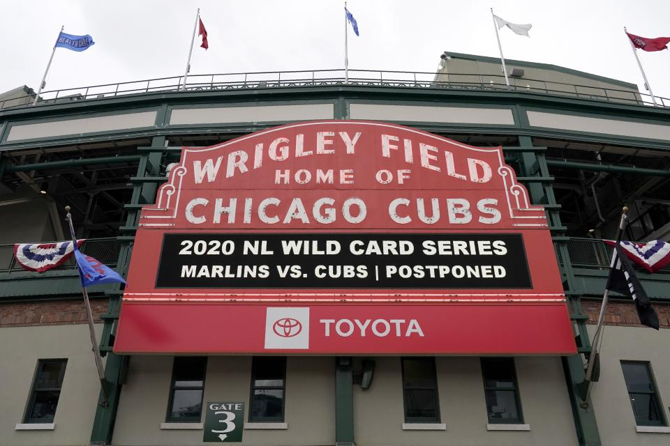 The marquis by Gate 3 at Wrigley field advises all who walk by that Game 2 of a National League wild-card baseball series between the Miami Marlins and Chicago Cubs has been postponed due to weather in Chicago, Thursday, Oct. 1, 2020. The game is scheduled to be played Friday. (AP Photo/Nam Y. Huh)
