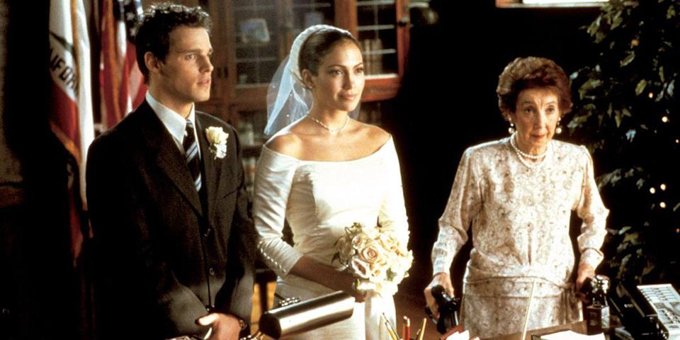 <p>As a wedding planner, Mary Fiore (Jennifer Lopez) knows that the devil is in the details. She elevated her courthouse nuptials to Massimo in <em>The Wedding Planner</em> with a boat-neck taffeta minidress and a veiled pillbox cap.<br></p>