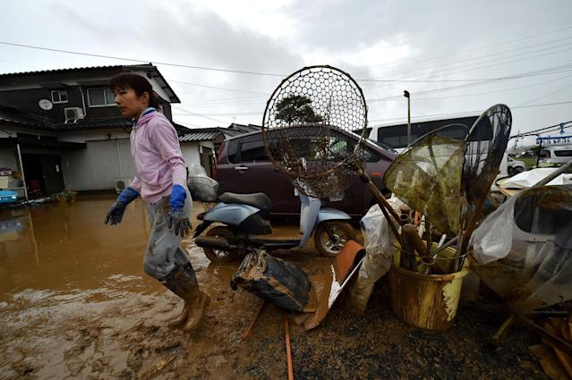 <p>A local resident takes out flood-damaged belongings from her house in Asakura, Fukuoka prefecture, on July 6, 2017.<br> (Photo: Kazuhiro Nogi/AFP/Getty Images) </p>
