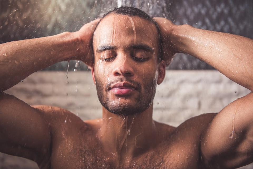man is taking shower in bathroom