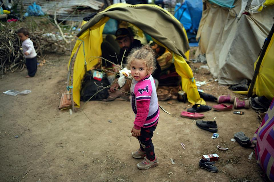 A child walks next to tends in a migrant camp set up near the Turkish-Greek border in March (Photo: ASSOCIATED PRESS)